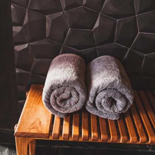 Two rolled grey towels on wooden bench in sauna. Spa in hotel